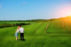 站立在领域的一对年轻夫妇,女孩亲吻男孩  库存照片