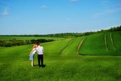 站立在领域的一对年轻夫妇,女孩亲吻男孩  库存图片