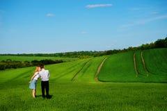 站立在领域的一对年轻夫妇,女孩亲吻男孩  免版税图库摄影