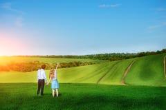 站立在领域的一对年轻夫妇,女孩显示她的手对天空 免版税库存图片