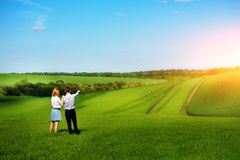 站立在领域的一对年轻夫妇,女孩显示她的手对天空 免版税图库摄影