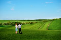 站立在领域的一对年轻夫妇,女孩显示她的手 库存照片