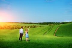 站立在领域的一对年轻夫妇,女孩显示她的手 免版税库存图片