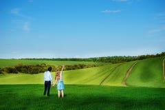 站立在领域的一对年轻夫妇,女孩显示她的手 库存图片