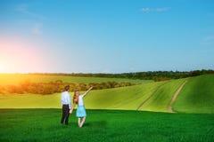 站立在领域的一对年轻夫妇,女孩显示她的手 免版税库存照片