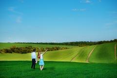 站立在领域的一对年轻夫妇,女孩显示她的手 免版税图库摄影