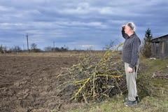站立在领域的农夫 免版税库存图片