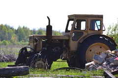 站立在领域的老黄色拖拉机 免版税库存图片