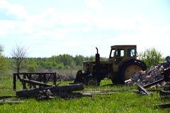 站立在领域的老黄色拖拉机 库存照片