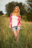 站立在领域的草的中美丽的女孩 库存照片