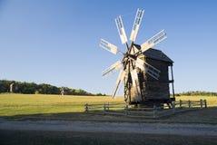 站立在领域的风车反对蓝天 免版税图库摄影