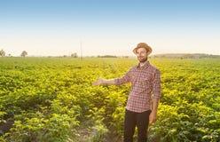 站立在领域风景前面的愉快的农夫 库存照片