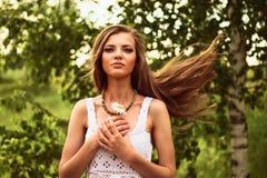 站立在风的愉快的年轻美丽的女孩室外,举行 免版税库存照片