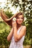 站立在风的愉快的年轻美丽的女孩室外 图库摄影