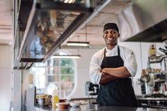 站立在餐馆厨房的厨师 免版税库存照片