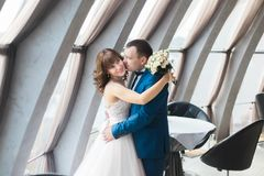 站立在餐馆窗口附近的拥抱的新婚佳偶的浪漫画象 图库摄影