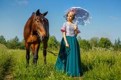 站立在马旁边的一件美丽的礼服的美丽的女孩 免版税图库摄影