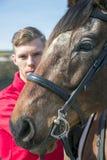 站立在马旁边的英俊的雄性马车手 免版税图库摄影