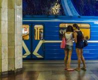 站立在骑马背景的地铁站的女同性恋的夫妇训练 库存图片
