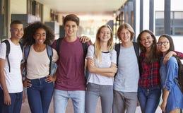 站立在高中走廊的少年同学 免版税图库摄影