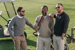 站立在高尔夫球场的不同种族的高尔夫球运动员 免版税库存照片