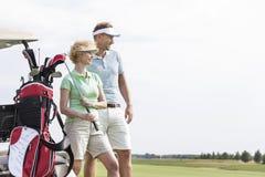 站立在高尔夫球场的微笑的男人和妇女反对清楚的天空 免版税库存照片