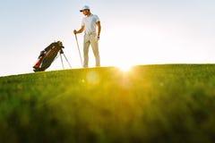 站立在高尔夫球场的男性高尔夫球运动员 库存图片
