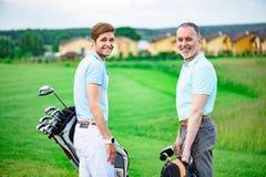 站立在高尔夫球场的高尔夫球运动员 免版税库存图片