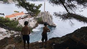 站立在高岩石和敬佩海的两个男孩背面图  站立两的兄弟剪影高在 股票视频