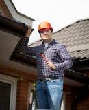 站立在高梯子和检查房子屋顶的杂物工 免版税库存照片