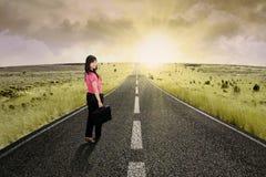 站立在高速公路路4的女实业家 免版税库存图片