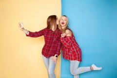 站立在黄色和蓝色墙壁的年轻愉快的妇女朋友的图象 库存照片