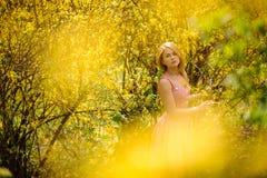 站立在黄色开花树之间分支的美丽的妇女  库存图片
