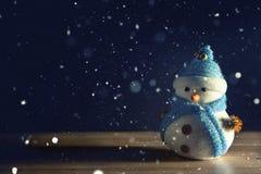 站立在黑暗的冬天圣诞节雪背景中的愉快的雪人 圣诞快乐和新年好贺卡与拷贝空间 图库摄影