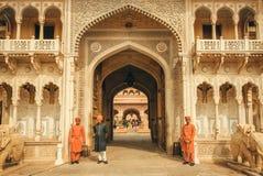 站立在18世纪城市宫殿入口门前面的印地安服装的战士在斋浦尔 免版税库存照片