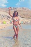 站立在水中和举在空气的比基尼泳装的美丽的被晒黑的女孩手 免版税库存照片