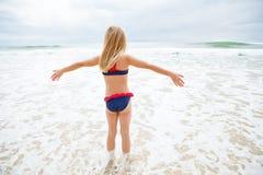 站立在水中的女孩在海滩 库存照片