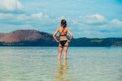 站立在水中的妇女在热带海滩旁边 免版税库存照片