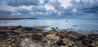 站立在水中的孤独的渔夫在Dor海滩,以色列 免版税库存照片