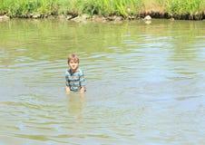 站立在水中的讨厌的男孩 免版税库存图片