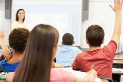 站立在类前面的老师问问题 免版税库存照片