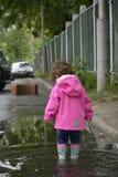 站立在水坑的小女孩 库存图片