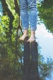 站立在水水坑的蓝色牛仔裤的赤足妇女在城市布局的 库存图片