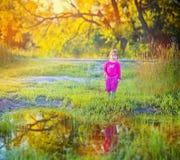 站立在水坑附近的逗人喜爱的小女孩 免版税库存照片