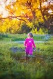 站立在水坑附近的逗人喜爱的小女孩 免版税库存图片