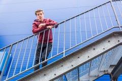 站立在紧急出口台阶的青少年的男孩  免版税库存照片