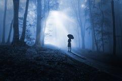 妇女在黑暗中的面对光 库存照片