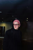 站立在黑暗的抽象背景的时兴的偶然年轻人 免版税库存图片
