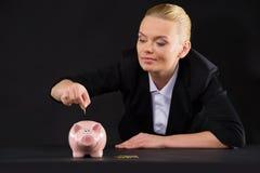 站立在黑暗的桌上的桃红色存钱罐 免版税图库摄影