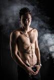 站立在黑暗的背景的精瘦的运动赤裸上身的年轻人 免版税库存照片